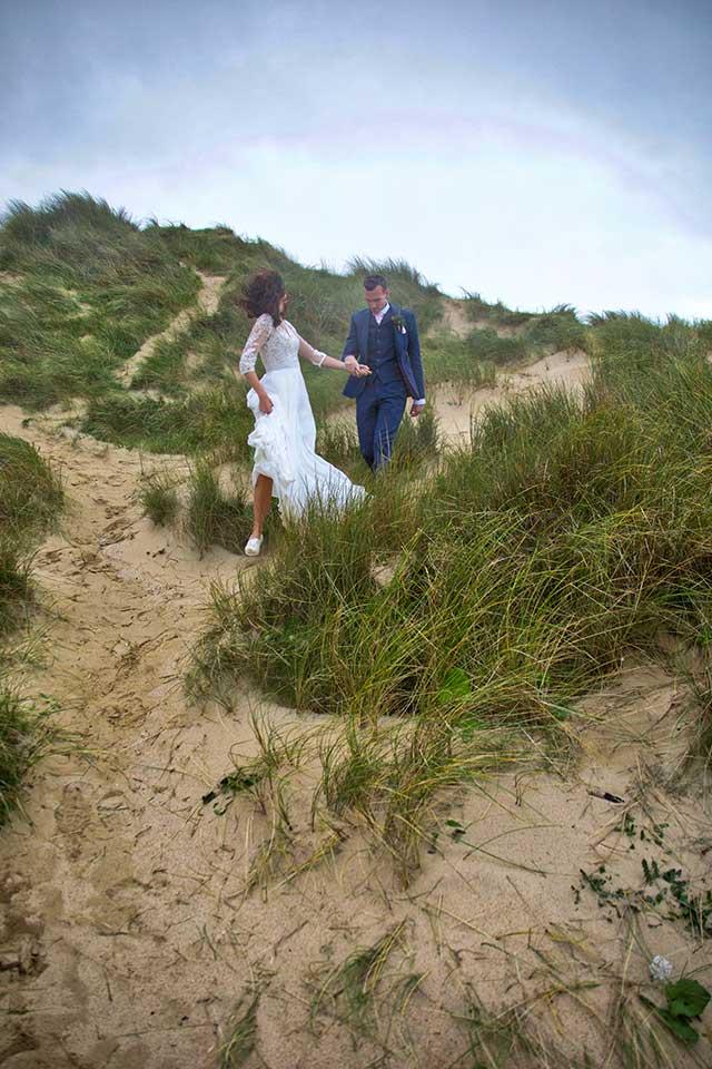 wedding couple walking in sand dunes
