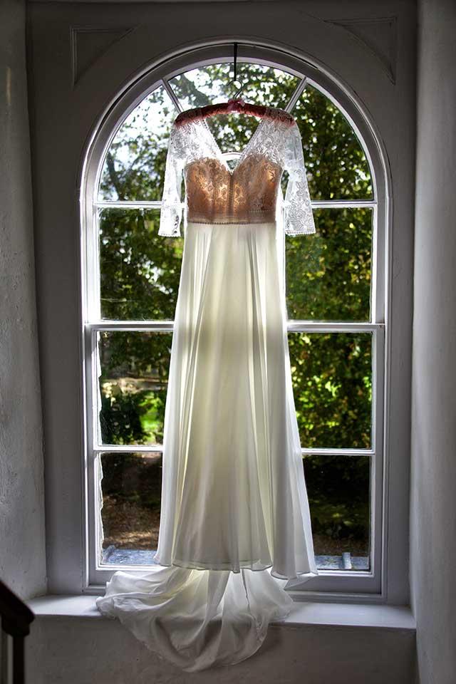 elegant white wedding dress hanging in Georgian house window