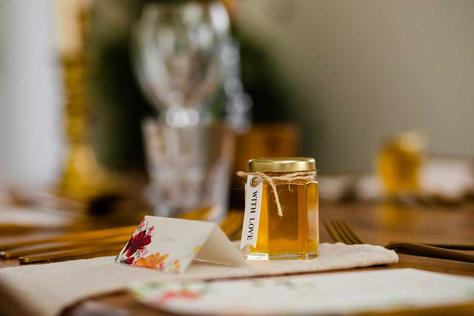 wedding table setting with jar of honey wedding favour