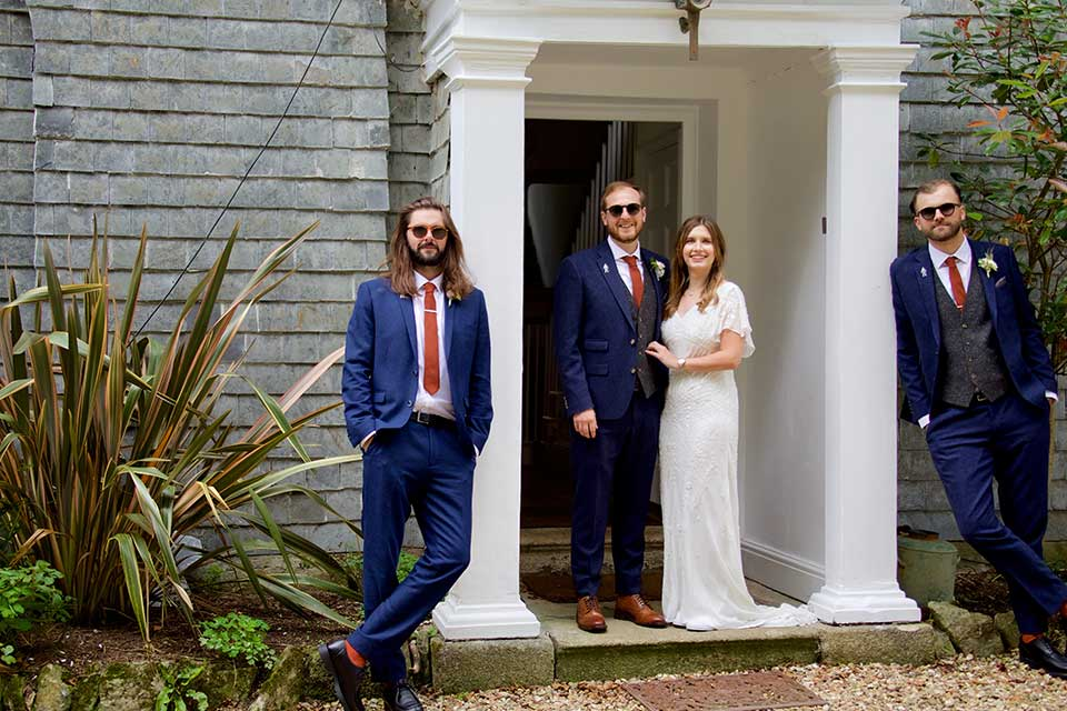 wedding guests at small wedding posing outside country house