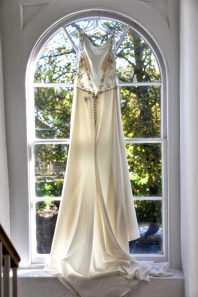 elegant wedding dress hanging in window at Georgian country house wedding venue