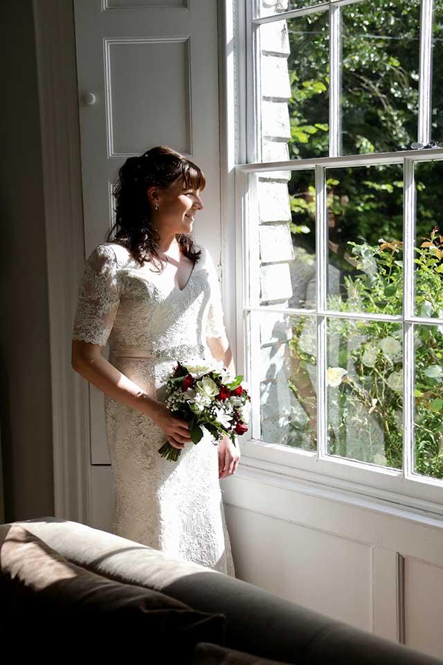 bride looking our of window at Georgian wedding venue