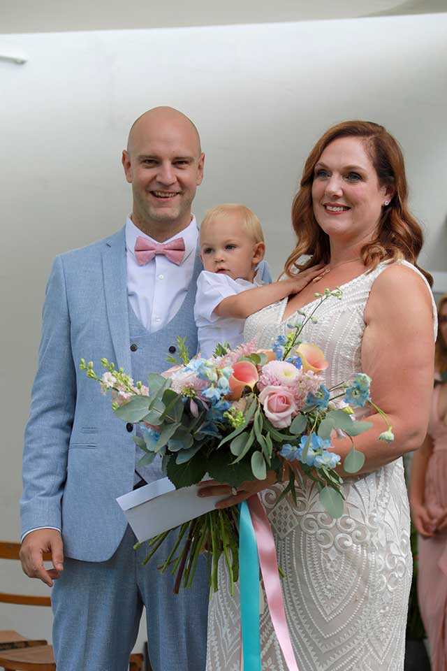 bride and groom and baby at wedding