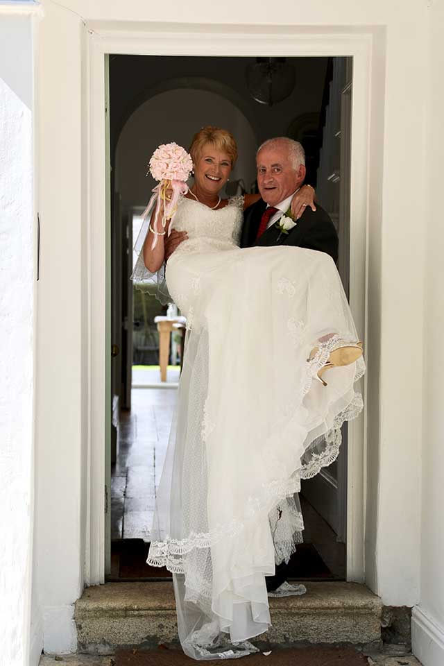 groom carrying bride over the threshold