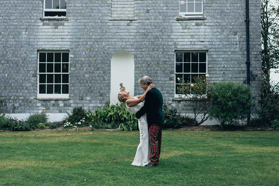bride and groom embrace in country house gardens