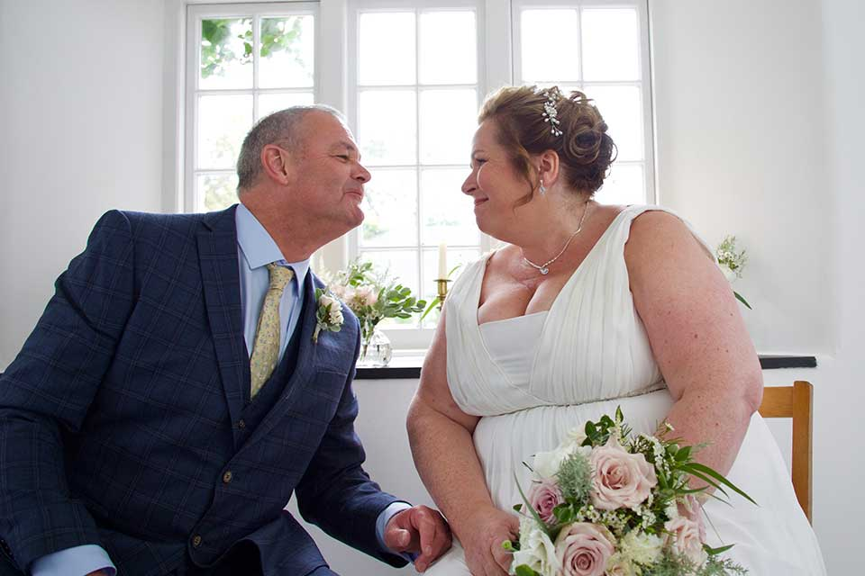 bride and groom smiling at eachother in front of sunny window