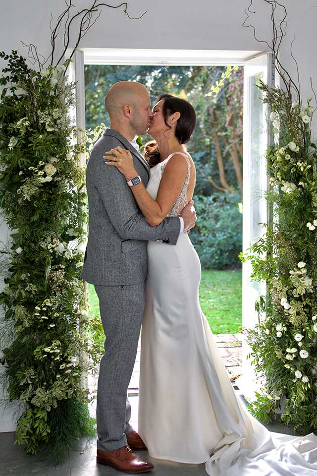 bride and groom kissing in front of floral installation