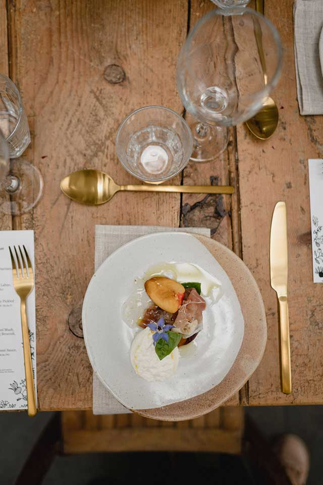 wooden table with styled wedding place setting
