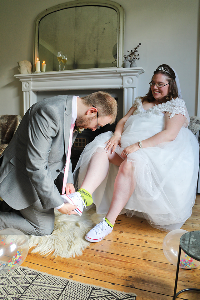 groom lacing up brides personalised wedding shoes