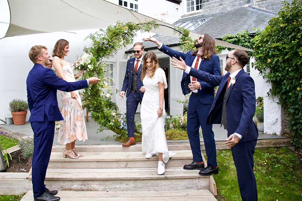 bride and groom walking down steps with guests throwing confetti