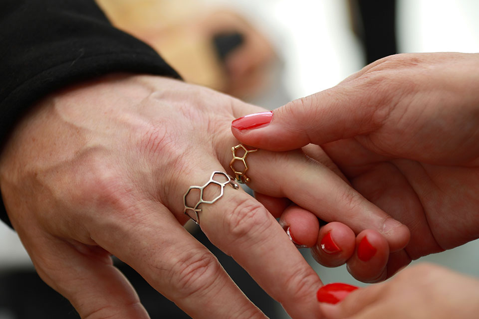 female hand putting wedding ring on male hand