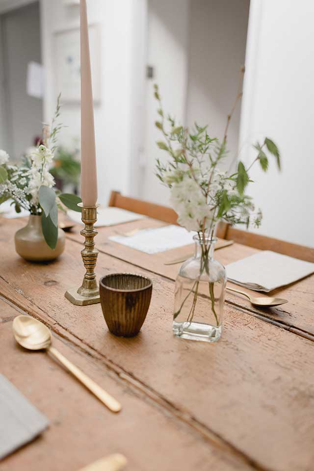 minimal wedding table setting with white flowers and candles