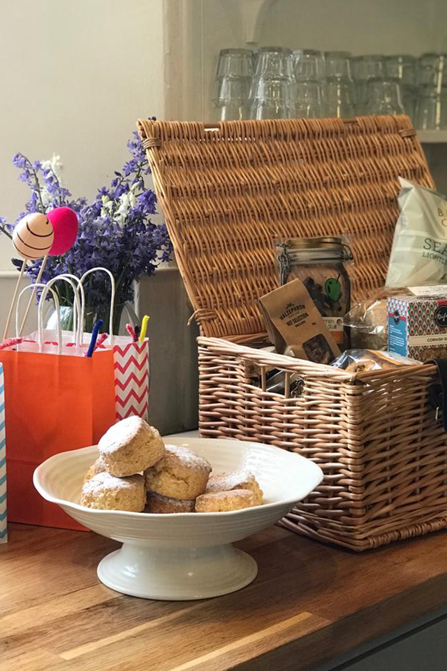 Wicker hamper with Cornish food and gifts welcome hamper next to freshly baked scones