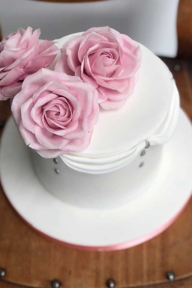 small wedding cake with white fondant icing and pale pink sugar flower roses