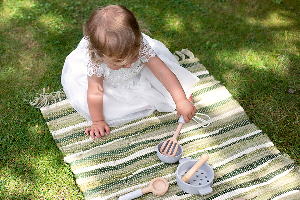 child in bridesmaid dress playing with wooden toys at small country wedding