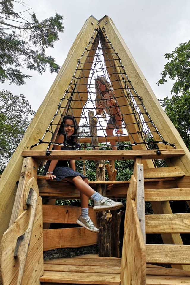 2 little girls having fun on wooden playground